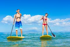Couple stand up paddle surfing in hawaii Stock Photos