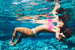Woman floating in tropical water Stock Photos