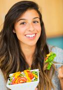 beautiful young woman eating a bowl of healthy organic salad - stock photo