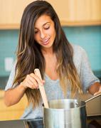 Woman cooking dinner Stock Photos