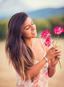 woman smelling flowers in nature - stock photo