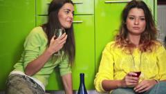 Girlfriends sitting on floor and drinking red wine HD Stock Footage