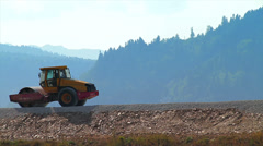 Compactor flattening road in rural area Stock Footage