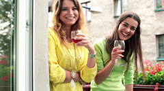 Two girlfriends raising toast to camera with glass of wine HD - stock footage