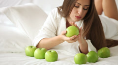 Pretty girl lying on bed with apples in front of her holding one and smiling  Stock Footage