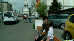 Dad and daughter talking on a bench at the Moscow city street Stock Footage