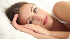 Beautiful girl lying in bed looking at camera closing her eyes and falling Stock Footage