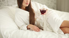 Beautiful girl lying in bed holding glass of wine looking at camera and smili Stock Footage