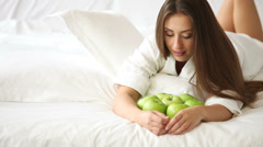 Cheerful girl lying on bed with lot of green apples holding one looking  Stock Footage
