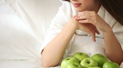 Charming young woman lying on bed with lot of green apples looking at camera  Stock Footage