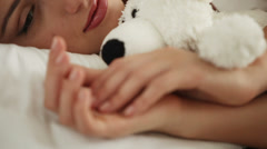 Cute young woman sleeping in bed hugging teddy bear waking up and smiling Stock Footage