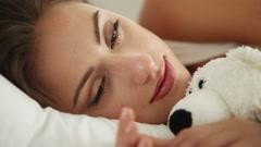Söpö nuori nainen nukkuu sängyssä halaa nalle herää ja hymyilee Arkistovideo