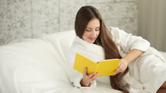 Cute girl in bathrobe lying in bed reading book closing it and smiling at camera Stock Footage