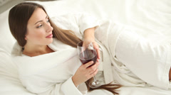 Cute girl lying in bed holding glass of wine looking at camera and smiling Stock Footage