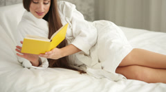 Pretty girl in bathrobe lying in bed reading book looking at camera and smiling Stock Footage