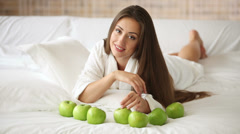 Cute girl in bathrobe lying on bed with green apples in front of her and smiling Stock Footage