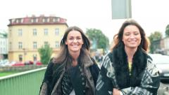 Two young happy girlfriends walking in the city HD Stock Footage