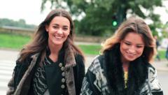 Happy girlfriends walking through street on zebra crossing HD Stock Footage
