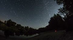 Timelapse of a starry night with a star trail effect with trees, river and fire  - stock footage