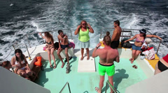 Tourists at the stern of the ship during a cruise along the sea shore Stock Footage