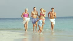Multi Generation Family Having Fun In Sea On Beach Holiday Stock Footage
