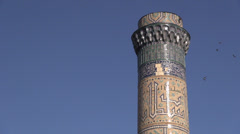 Birds fly around minaret, Samarkand, Uzbekistan Stock Footage