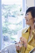 Young woman by window - stock photo