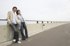 Young couple leaning on a fence - stock photo