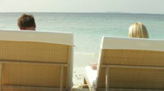 Couple Relaxing On Sun Loungers Stock Footage