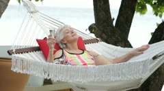 Senior Woman Relaxing In Beach Hammock With Champagne Stock Footage
