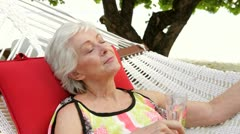 Senior Woman Relaxing In Beach Hammock With Champagne - stock footage