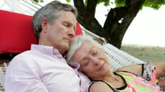 Senior Couple Relaxing In Beach Hammock - stock footage