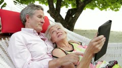 Senior Couple Relaxing In Beach Hammock Using Digital Tablet - stock footage