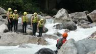 Group of tourists jumping into a waterfall locked down Stock Footage
