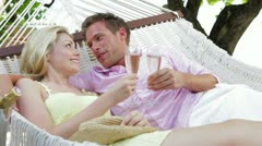 Couple Relaxing In Beach Hammock Drinking Champagne - stock footage