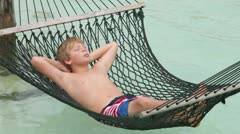 Boy Relaxing In Beach Hammock Stock Footage