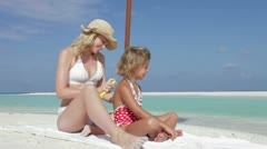 Mother Protecting Daughter With Sun Lotion On Beach Holiday Stock Footage