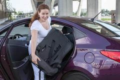 Woman with baby safety seat placing it in the car Stock Photos