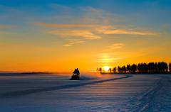 Blue and orange sunset on winter snowy lake and snowmobile with people on it. Stock Photos