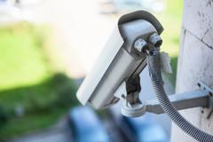 Video surveillance camera on a wall of the building, close up view Stock Photos