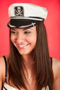 Woman in marine pirate service cap. face portrait on red background. Stock Photos