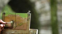 Artist paints stone historic bridge Stock Footage