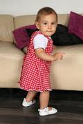 Baby girl tries to walk Stock Photos