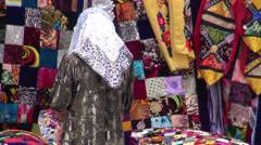 Woman with headscarf buys colorful textile Stock Footage