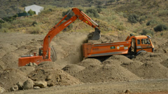 Excavator and truck moving land Stock Footage