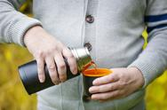 Stock Photo of Man pouring tea at outdoors in autumn