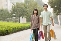 Young couple walking with shopping bags in hands, Beijing, China - stock photo