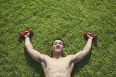 Shirtless Man Lying in Grass with Dumbbells in Beijing Stock Photos