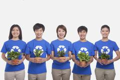 Group of people holding plants, studio shot Stock Photos