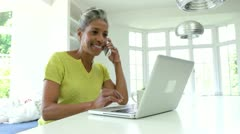 Stock Video Footage of Woman Using Laptop And Talking On Phone In Kitchen At Home
